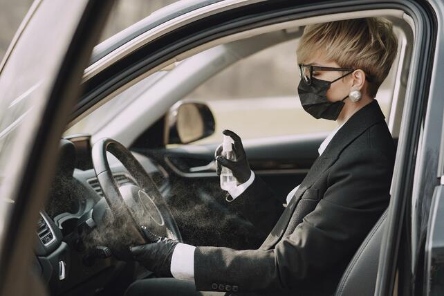 woman-in-formal-clothes-disinfecting-steering-wheel-of-car-4127517